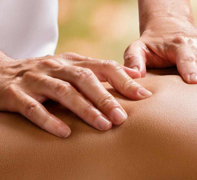 Hände eines Masseurs auf Frauenrücken